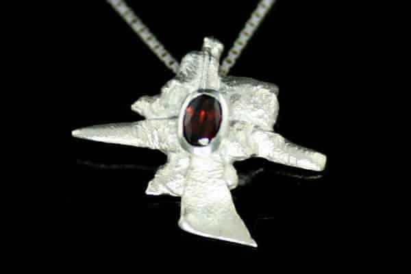 Arctic anheng i sølv med en oval granat. Smykket er kokt i syre for å få en ekstra hvit og matt overflate.